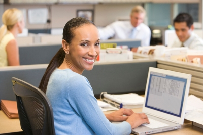 Businesswoman in cubicle using laptop smiling